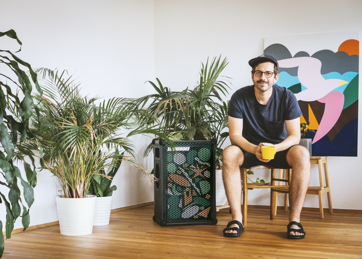 man sitting on a chair with a coffee cup next to a limited edition artist grill soundboks