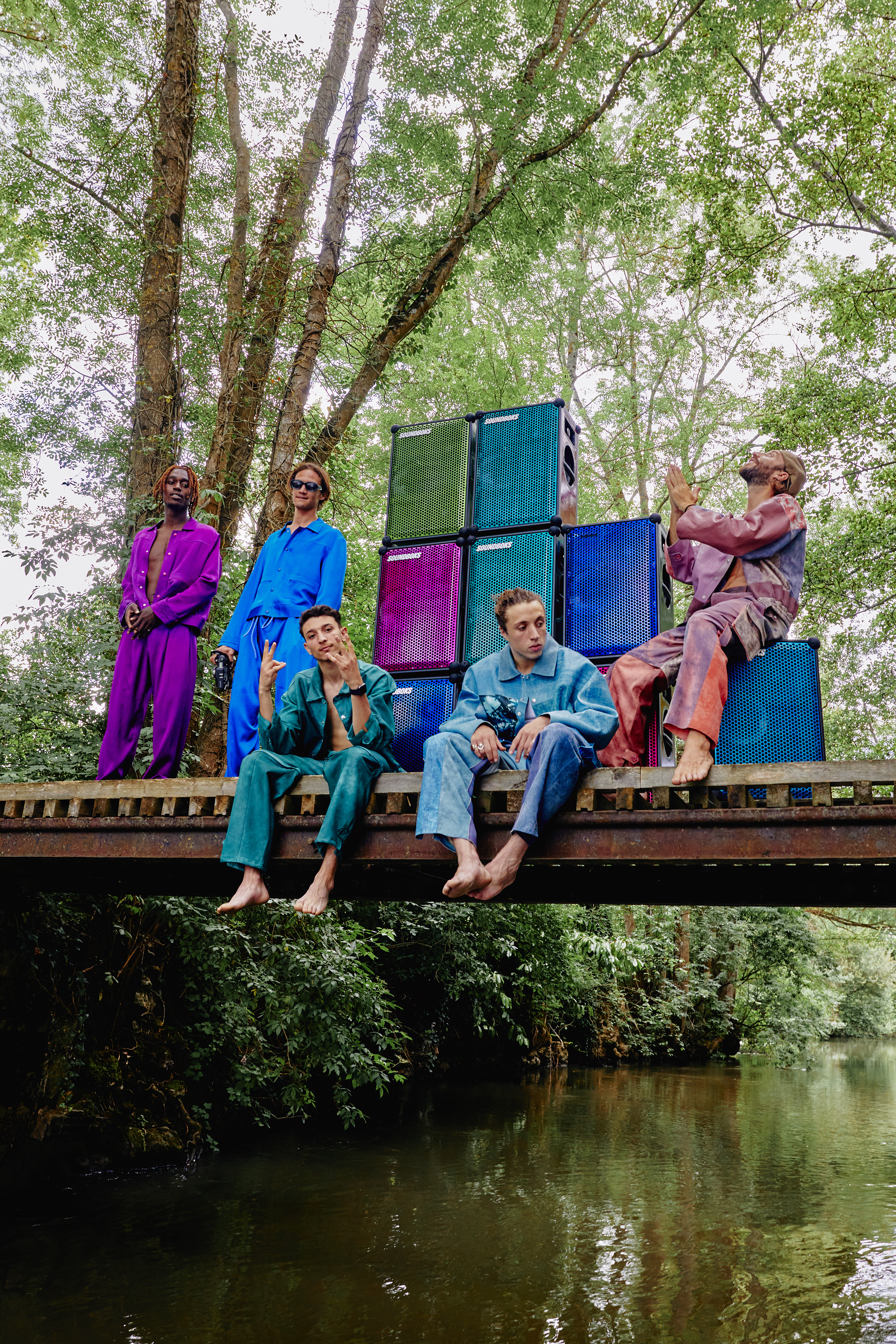 people sitting on a bridge with a bunch of speakers in various colors