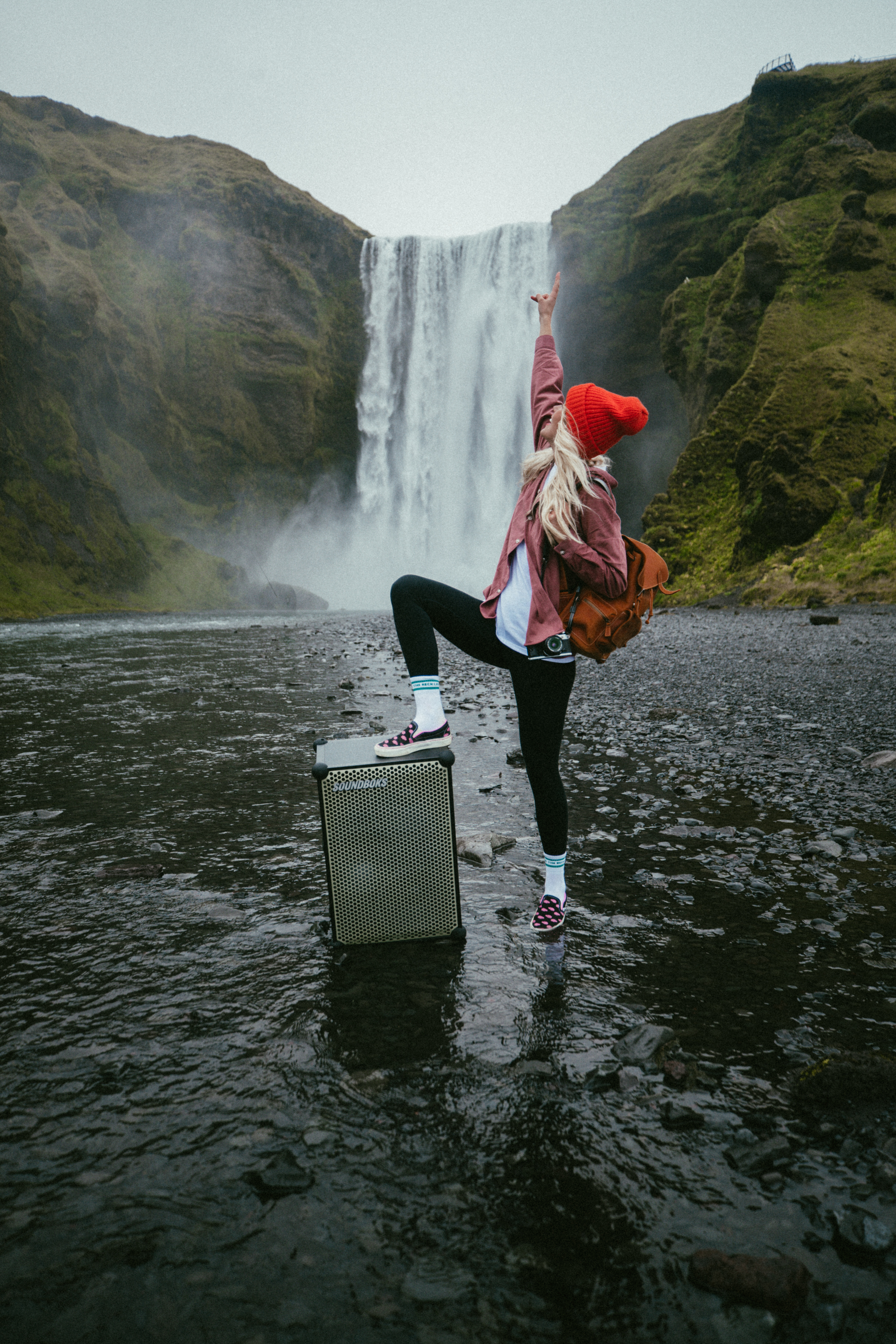Social media influencer, Asa, in iceland with a SOUNDBOKS martian edition in front of a waterfall.