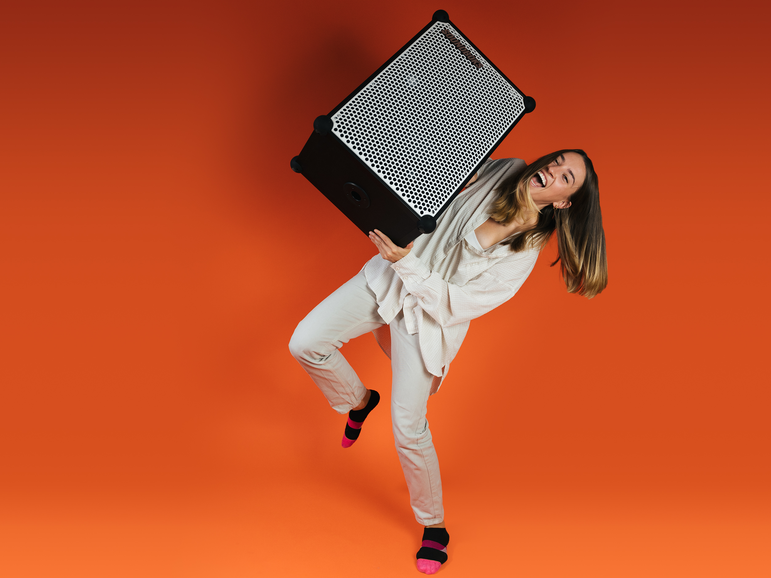 Kait, Brand Experience Team Lead at SOUNDBOKS in front of an orange background with a white SOUNDBOKS in her hands
