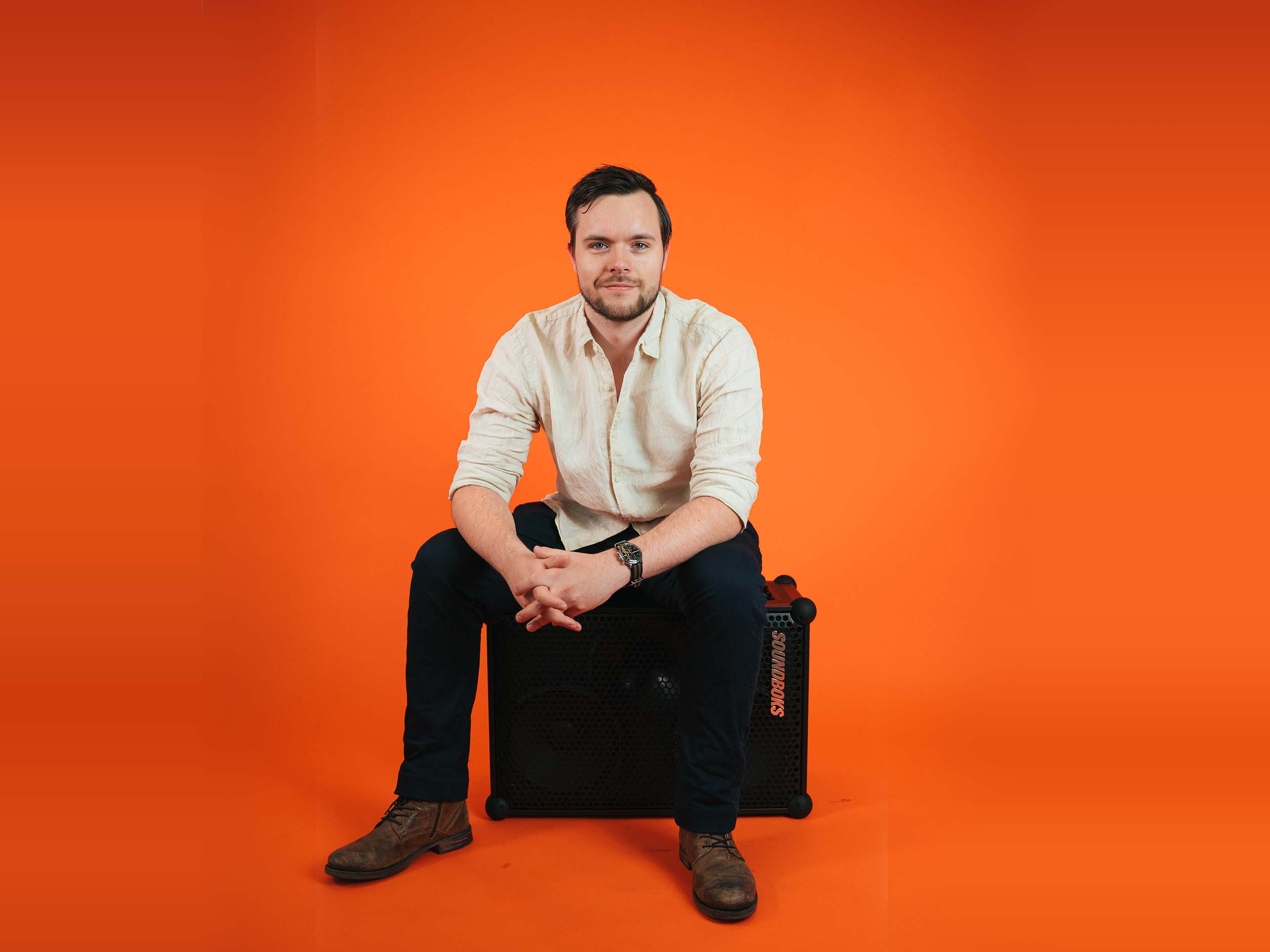 Rene sitting on a SOUNDBOKS in front of an orange background