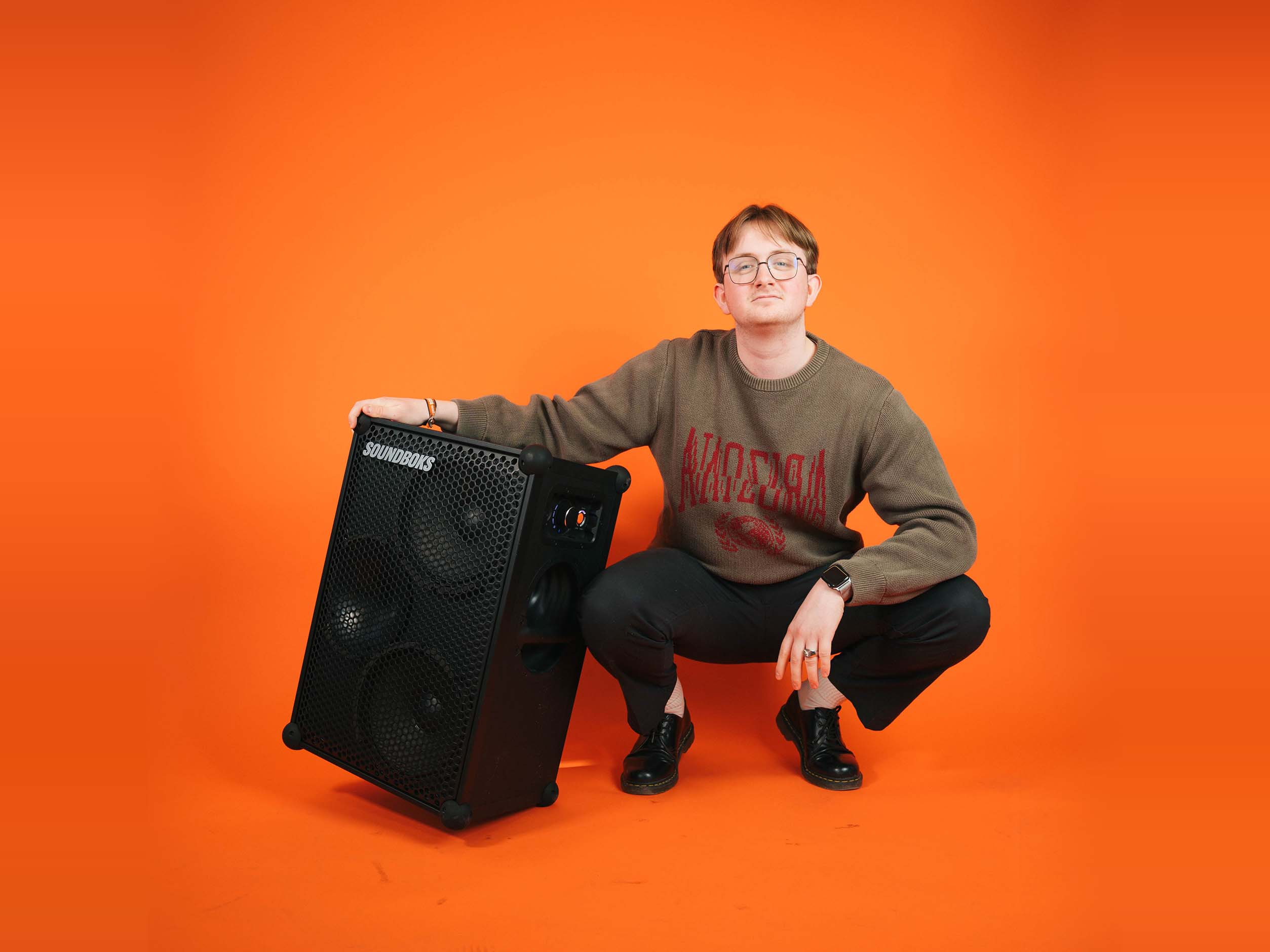 Rasmus sitting with a SOUNDBOKS in front of an orange background