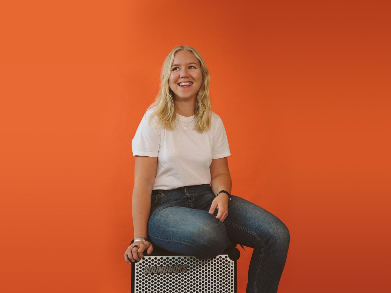 Gesche, blonde girl sitting on a white SOUNDBOKS