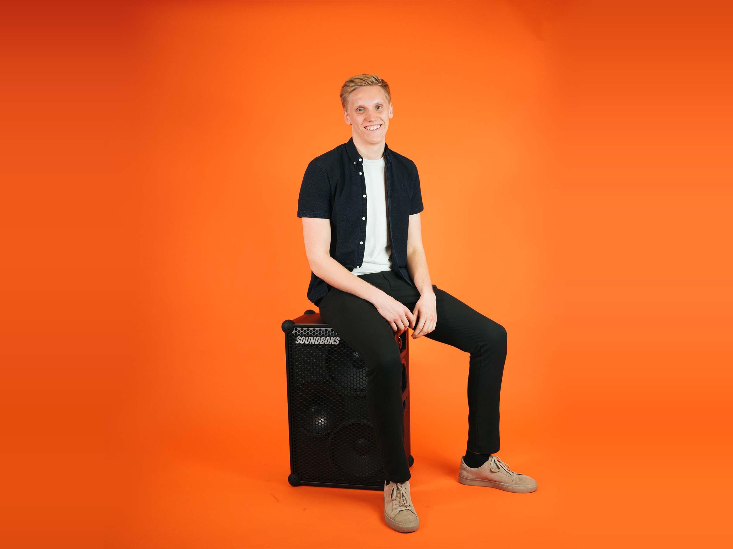 Sebastian soundboks employee, sitting with a SOUNDBOKS in front of an orange background