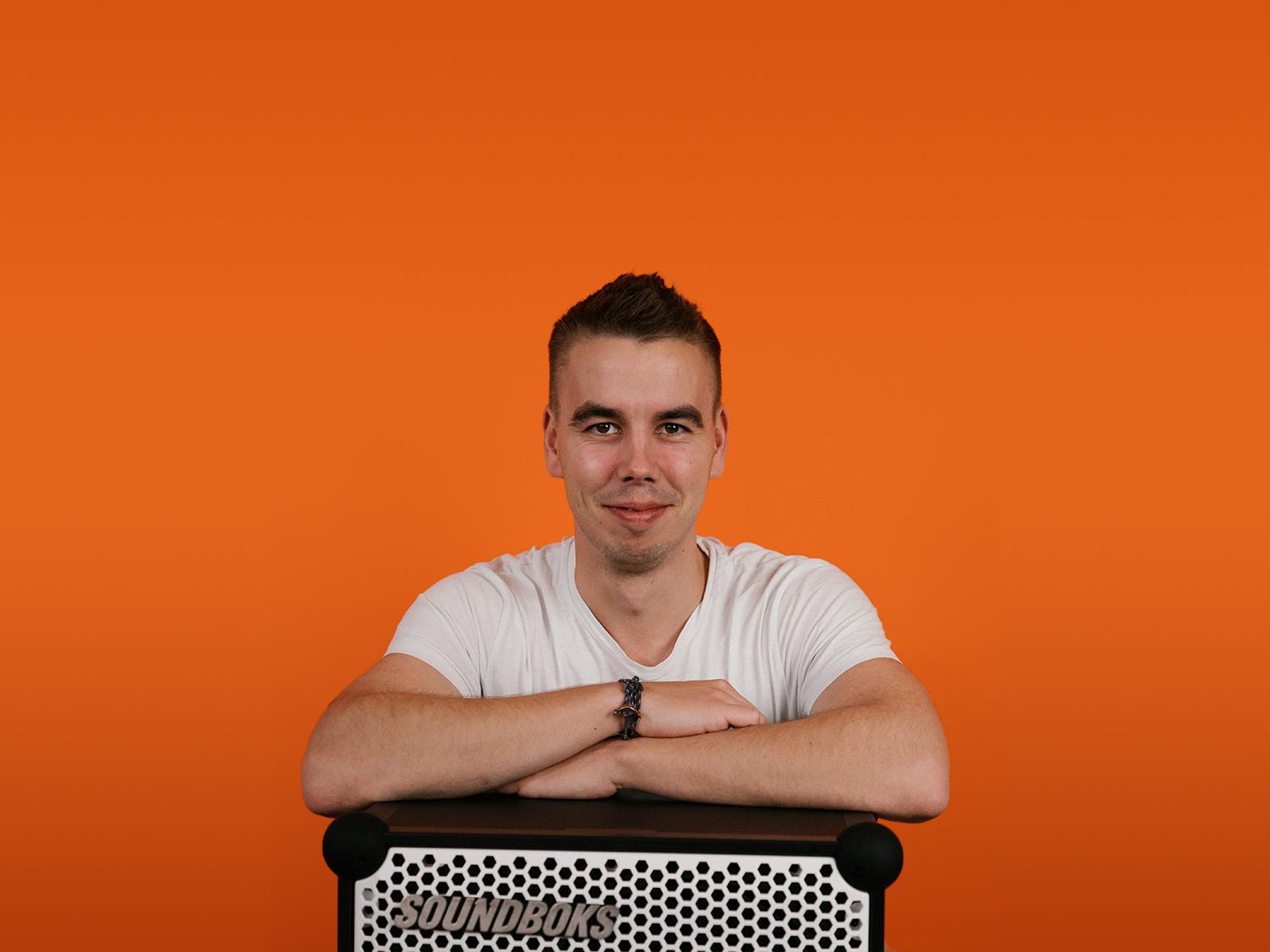 emil, a supply chain coordinator at soundboks leaning on top of a soundboks speaker