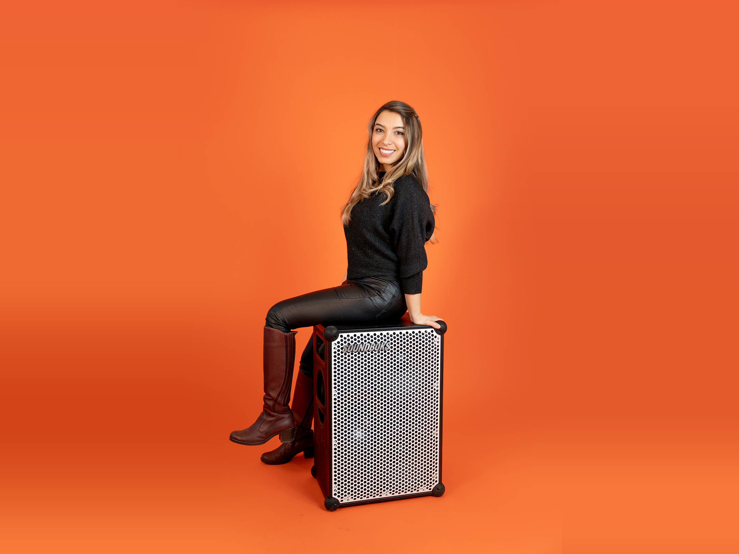 Mehrzad, in a black outfit sitting on top of a SOUNDBOKS in front of an orange background