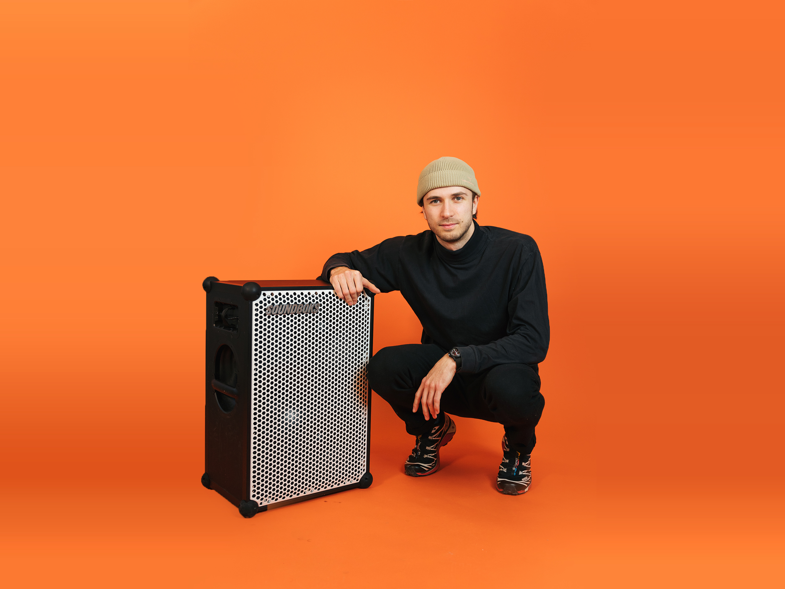 Alfred sitting next to a SOUNDBOKS in front of an orange background