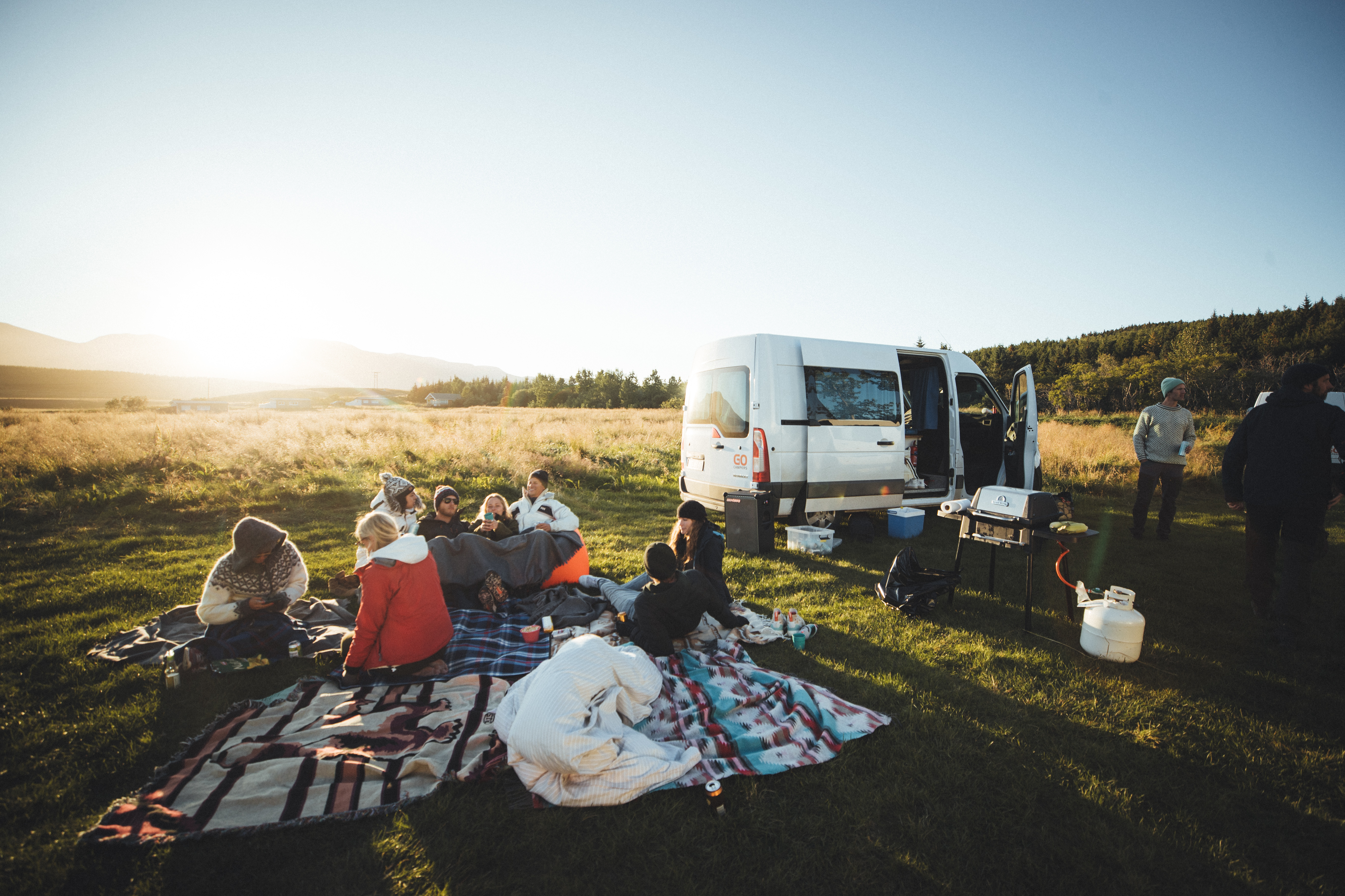 people having a picnic in front of a white sprinter van with a soundboks listening to music