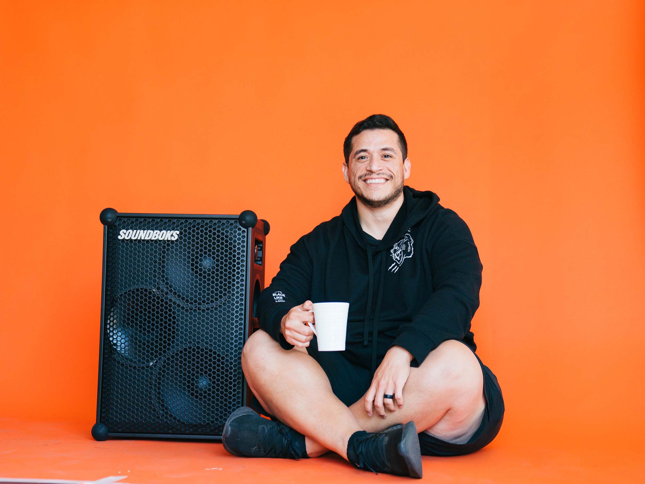 Matthew drinking a cup of coffee next to a SOUNDBOKS speaker