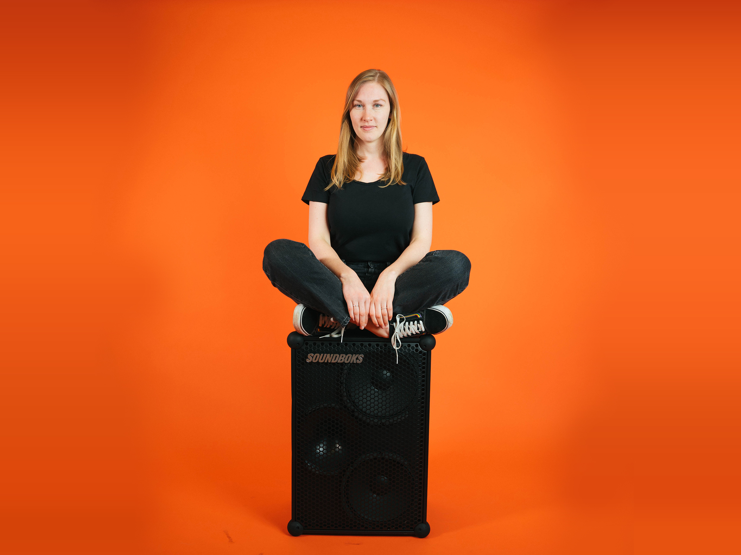 Michelle, a soundboks employee sitting on top of a soundboks in front of an orange background