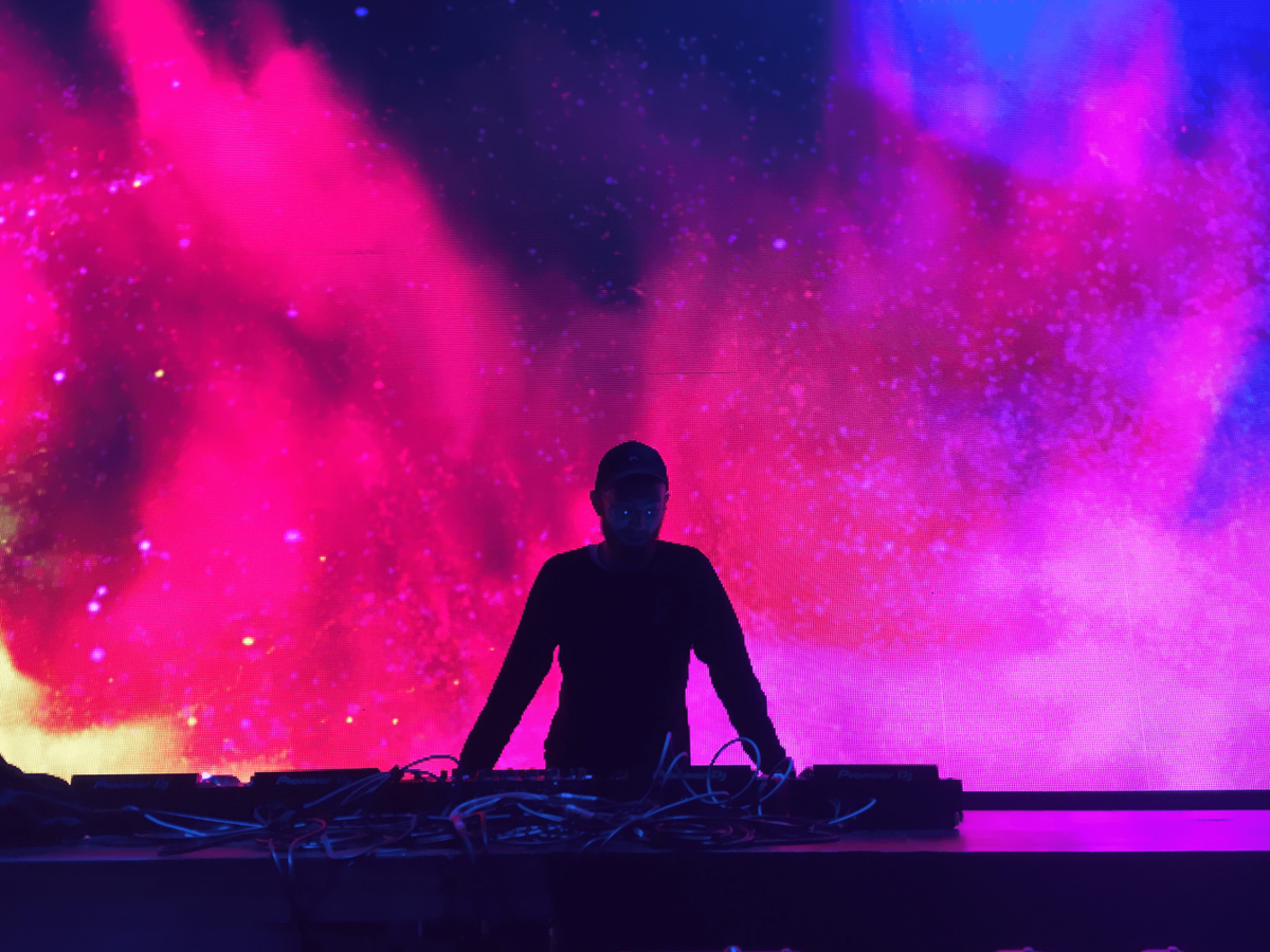 DJ in front of coloured lights