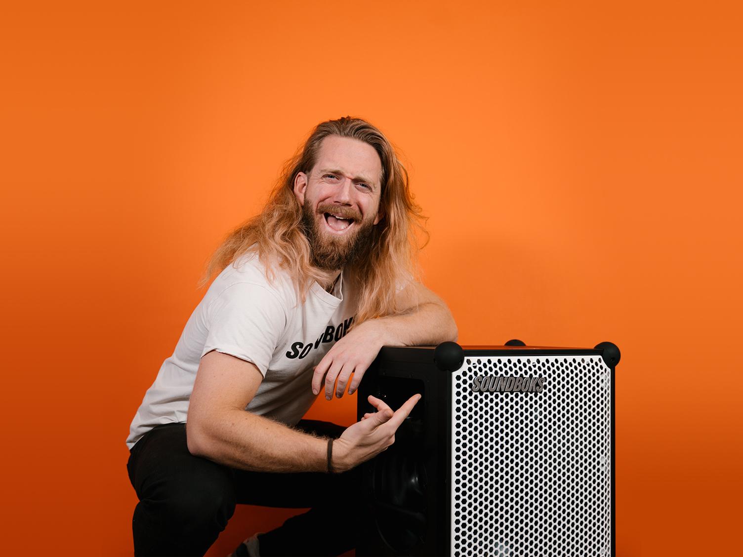 Kalle, Digital Project Lead at SOUNDBOKS in front of an Orange Background.