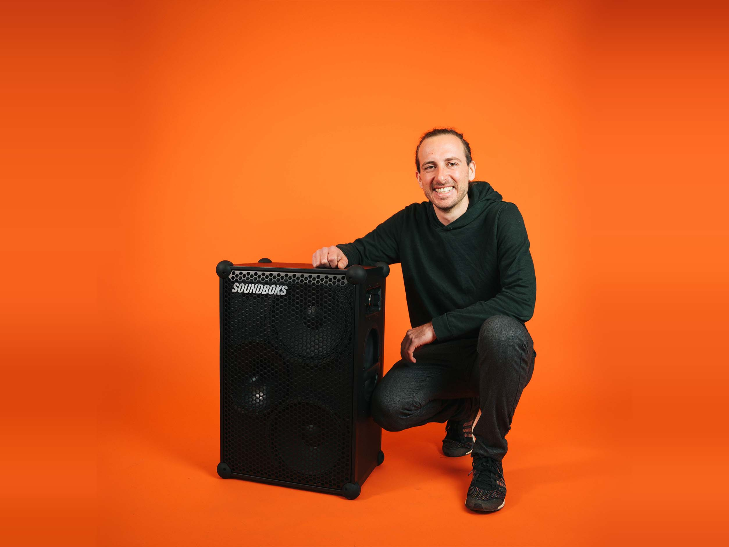Stephan soundboks employee, sitting with a SOUNDBOKS in front of an orange background