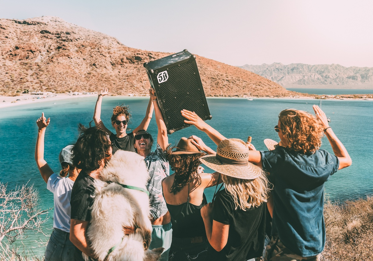 group of people partying by a lake with a SOUNDBOKS speaker