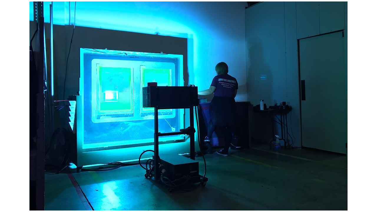 A woman exposing screens at a screen printing shop.