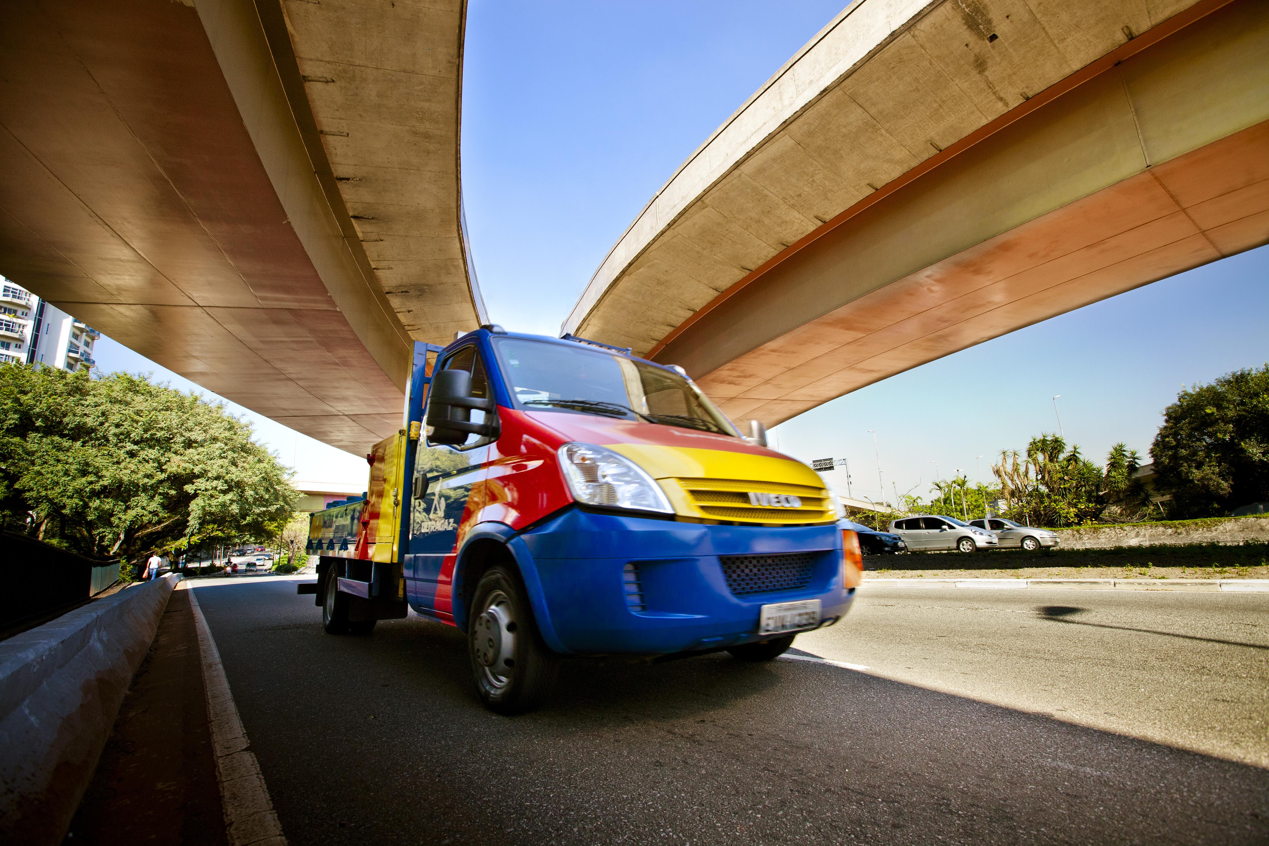 Foto de caminhão da Ultragaz nas cores azul, amarela e vermelha embaixo de um viaduto com carros e árvores ao fundo em um dia muito iluminado.
