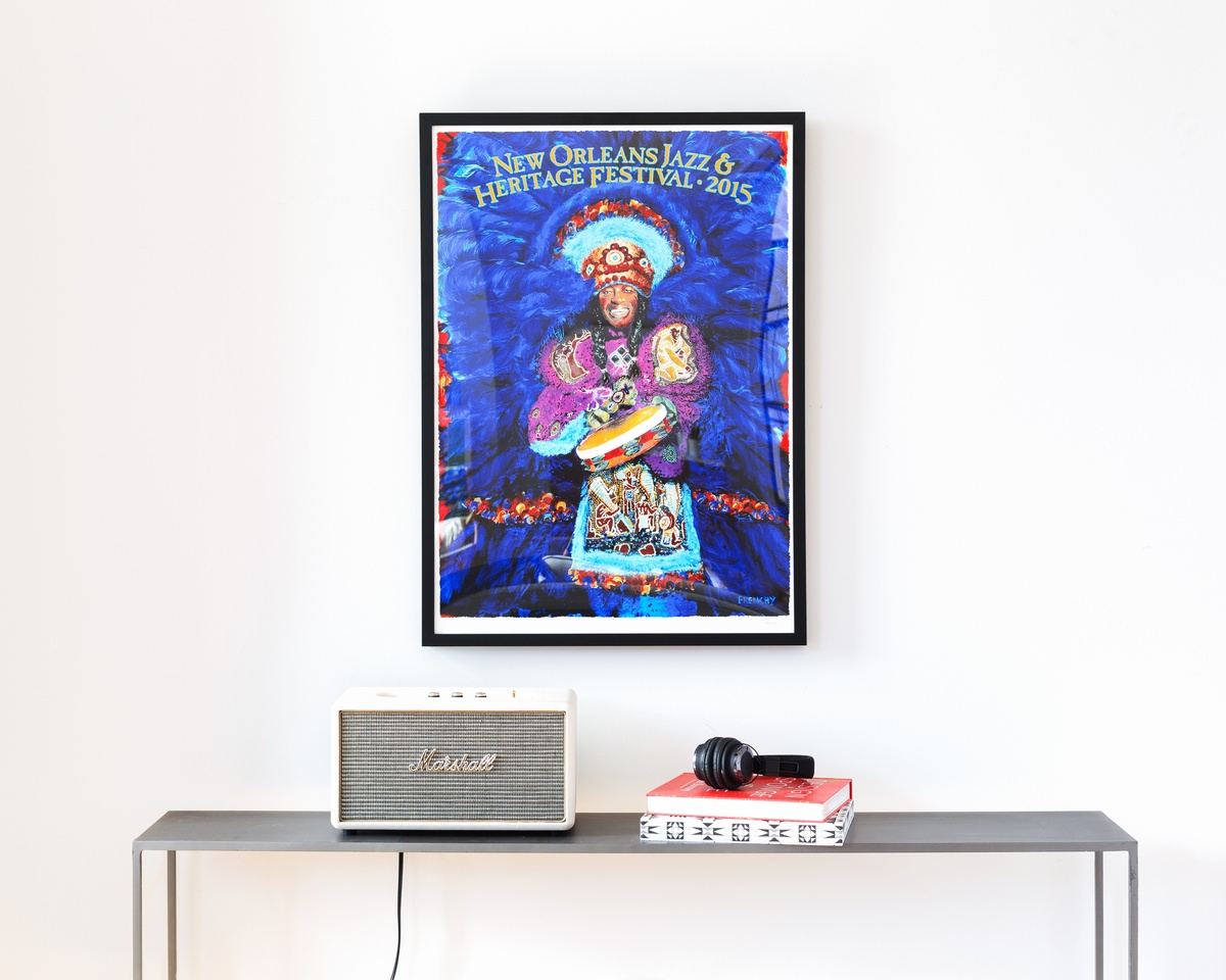 large, colorful poster on black frame over a table with an amp and headphones