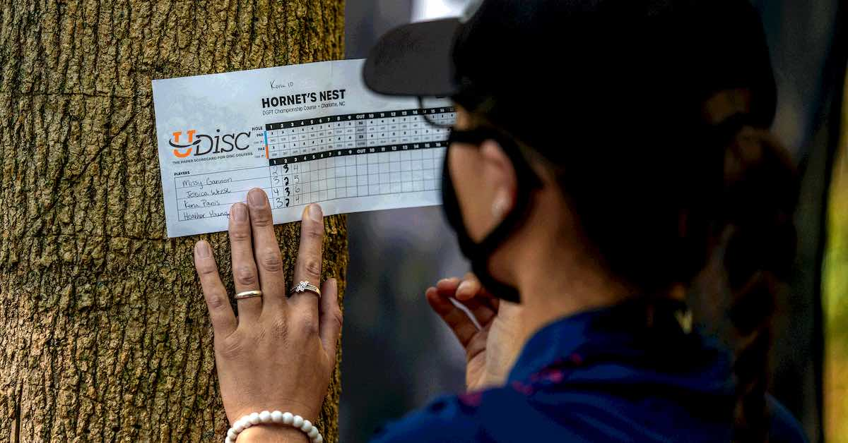 A woman writes on a paper scorecard on a tree