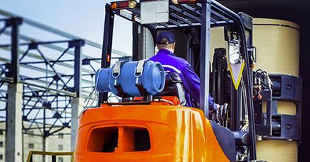 Imagem de um funcionário dirigindo uma empilhadeira com um botijão de 20 kg na carroceria.
