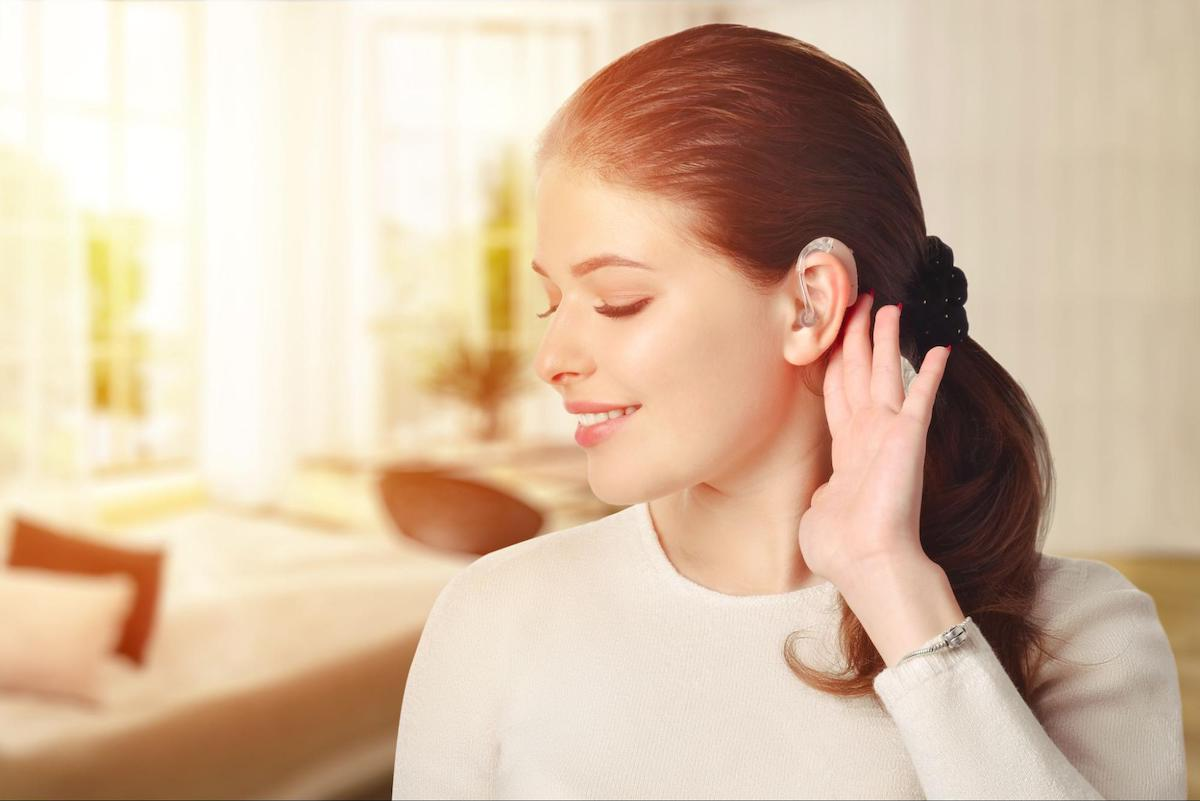 Amplifon: Smiling woman wearing a hearing aid with her eyes closed while holding her ear
