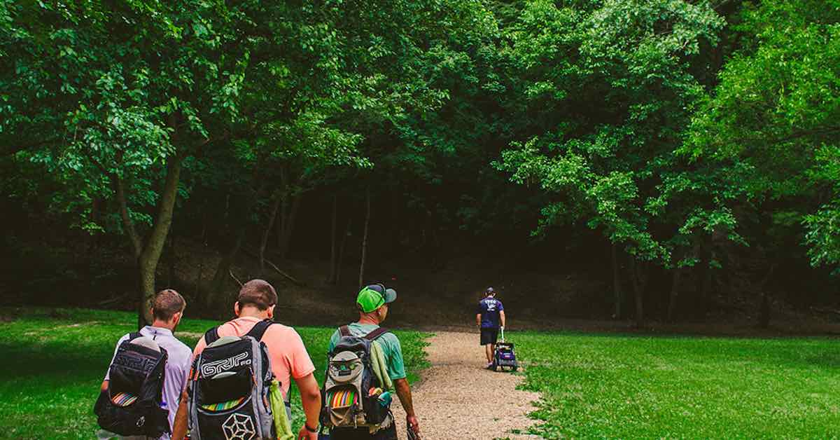 People with disc golf backpacks walking from a field into dark woods