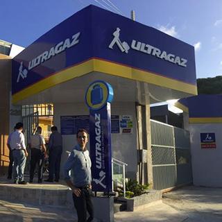 Foto da fachada de uma revenda Ultragaz durante o dia com a marca estampada nas cores azul, vermelho e amarelo, com um homem em frente  e ao fundo 4 homens adentrando a revenda.