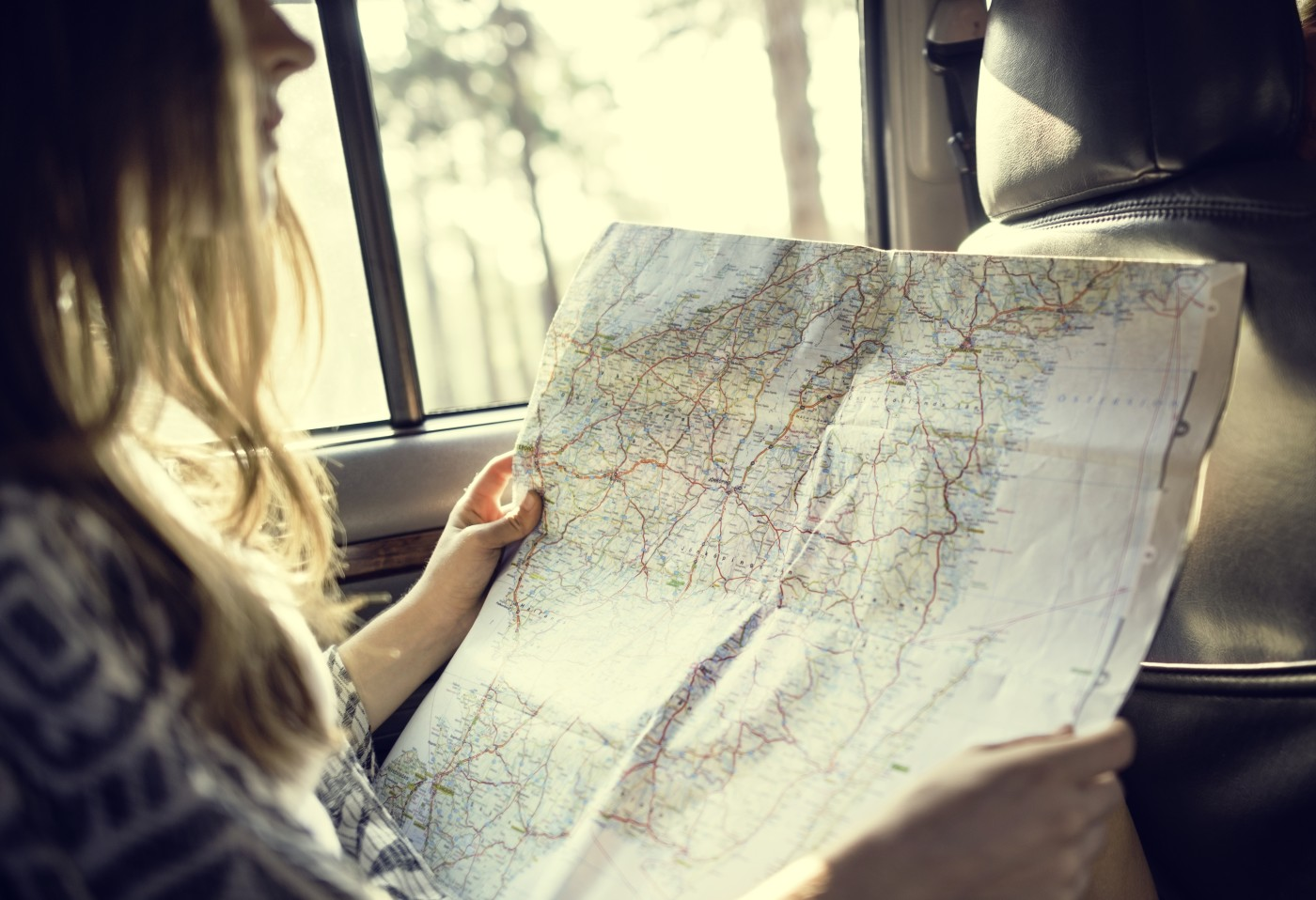 girl in car looking at map