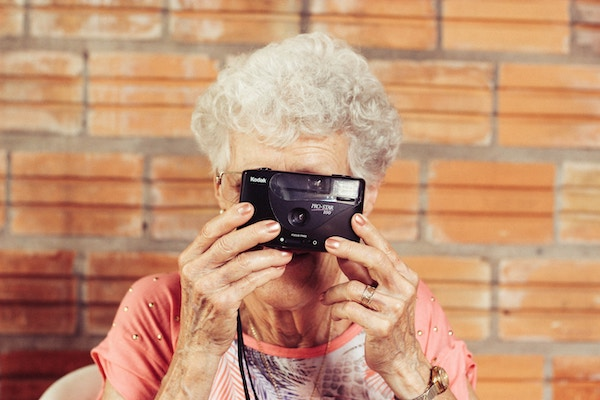 elderly woman-nursing home resident with camera as part of activities provided by the activities director