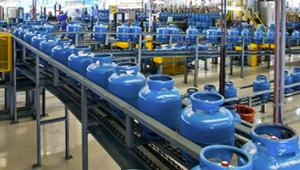 Foto da linha de produção onde fica o envasamento dos botijões azuis. Estão todos em fileira na esteira das máquinas que fazem esse processo.