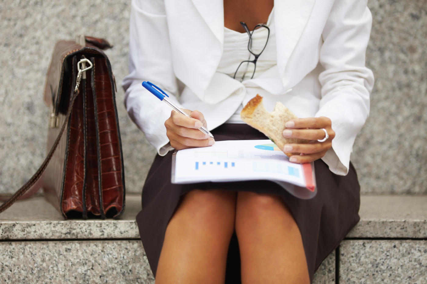 Business Woman Eating Lunch Outdoors And Reviewing Documents