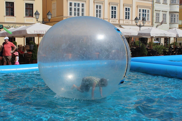 a boy in a bubble in a swimming pool