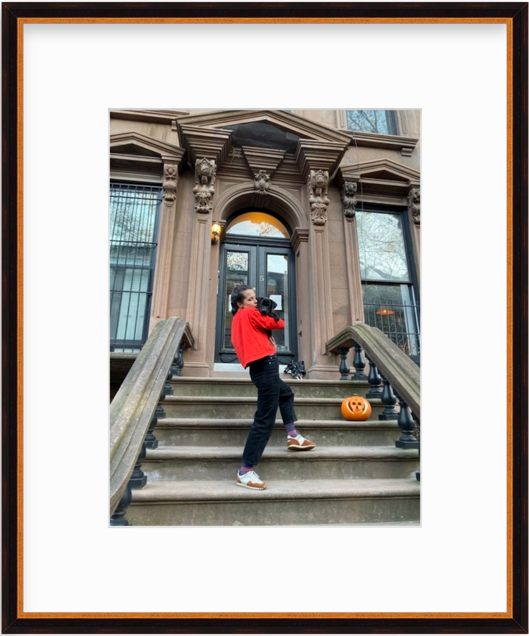 photo of woman with dog on stairs to brownstone in gold and black frame