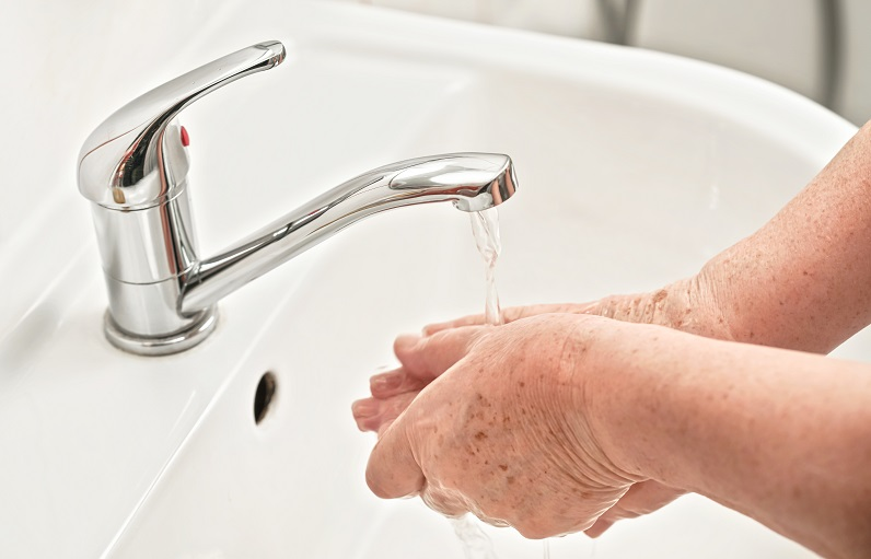 older adult cleaning hands to prevent covid-19 coronavirus infection from spreading