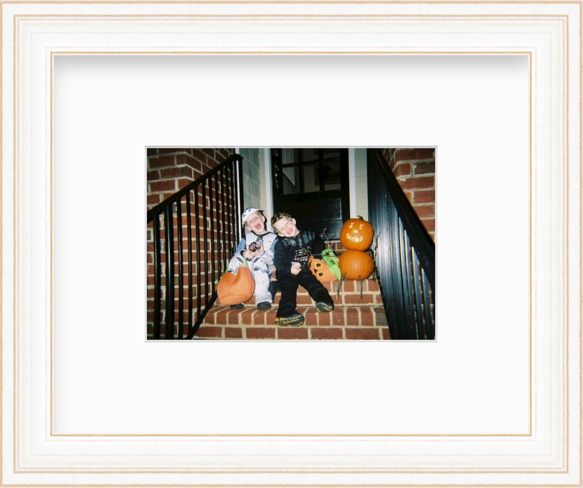 Photo of two boys in halloween costume on stoop in white frame