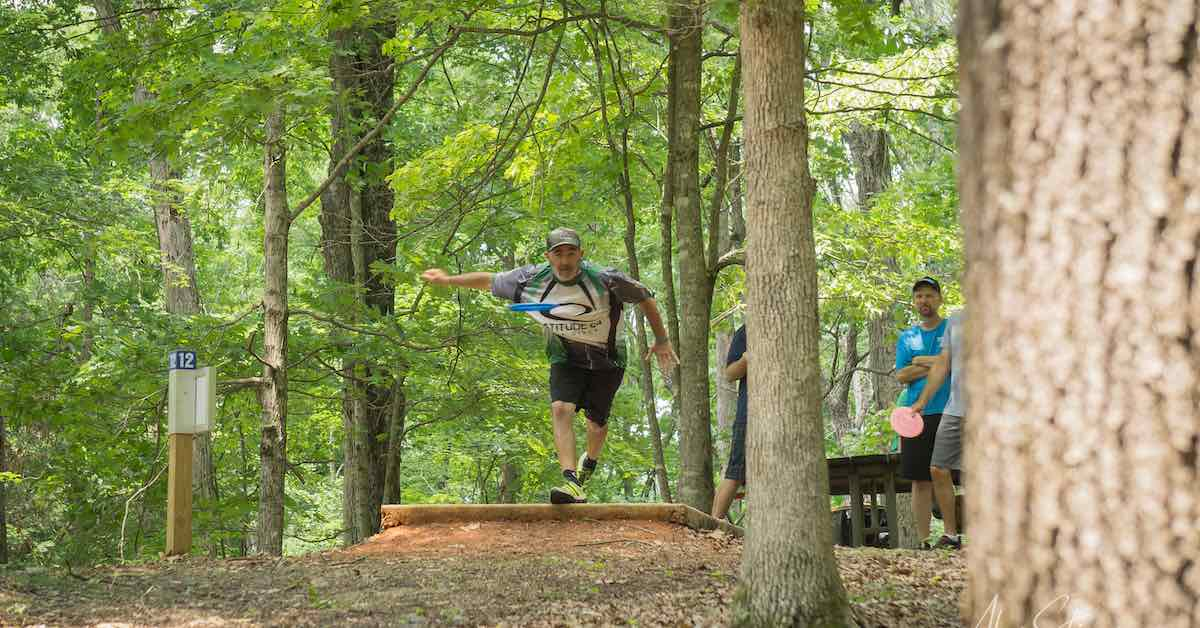 Pro disc golfer JohnE McCray throws off a tee pad at a wooded course