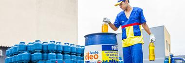 Foto de um homem branco vestido com uniforme da Ultragaz nas cores azul, vermelho e amarelo segurando duas latas de óleo com vários botijões de 13kg ao fundo.o