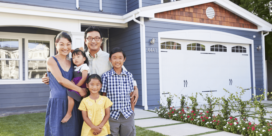 family of five outside of home with garage