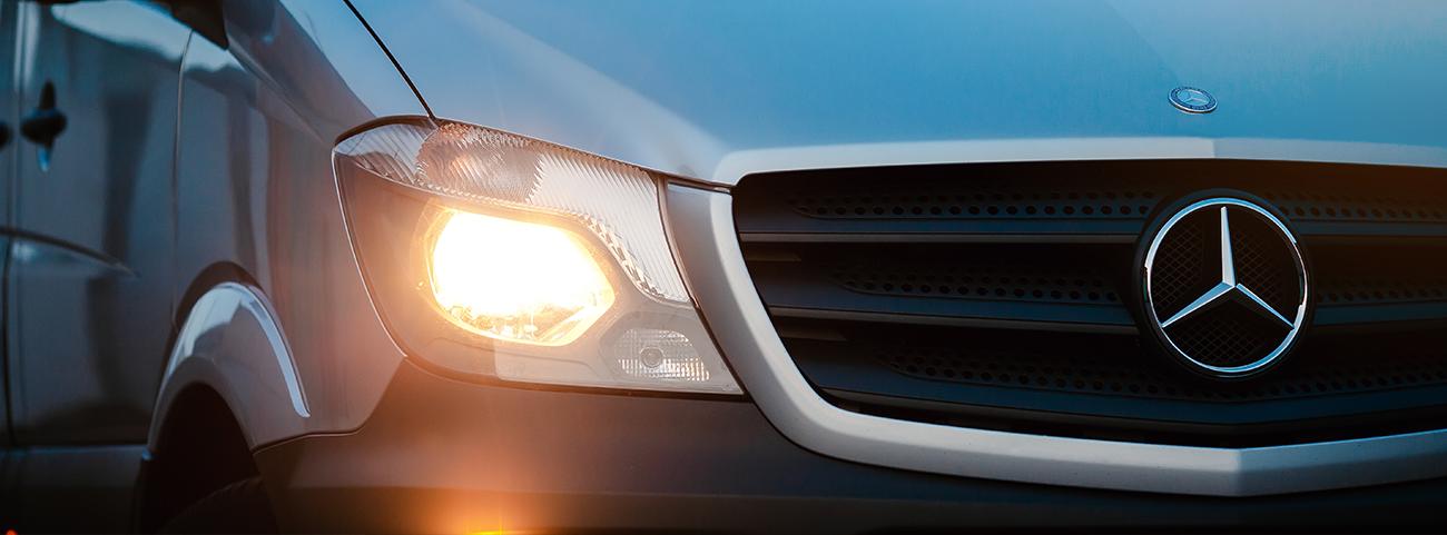 Camioneta Mercedes Benz plateada con las luces delanteras encendidas