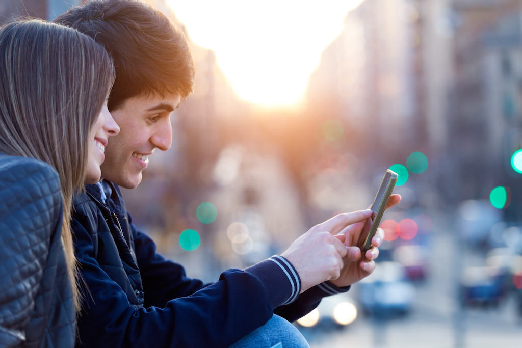 couple pointing and smiling at a phone