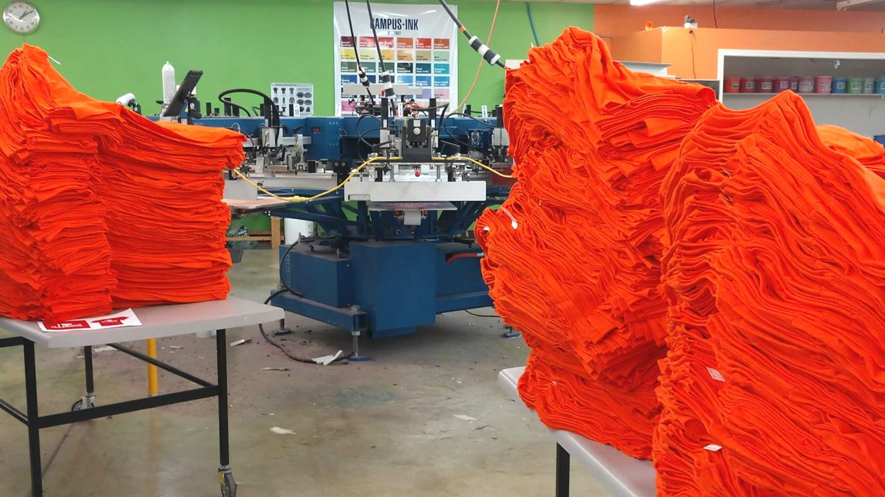 Stacks of orange Next Level shirts waiting to be screen printed.