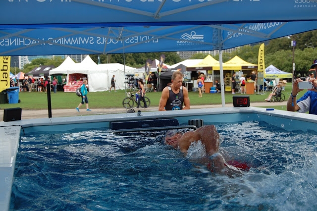 An age-group triathlete swimming in the High Performance Endless Pool at the ITU World Triathlon Grand Final Chicago Expo