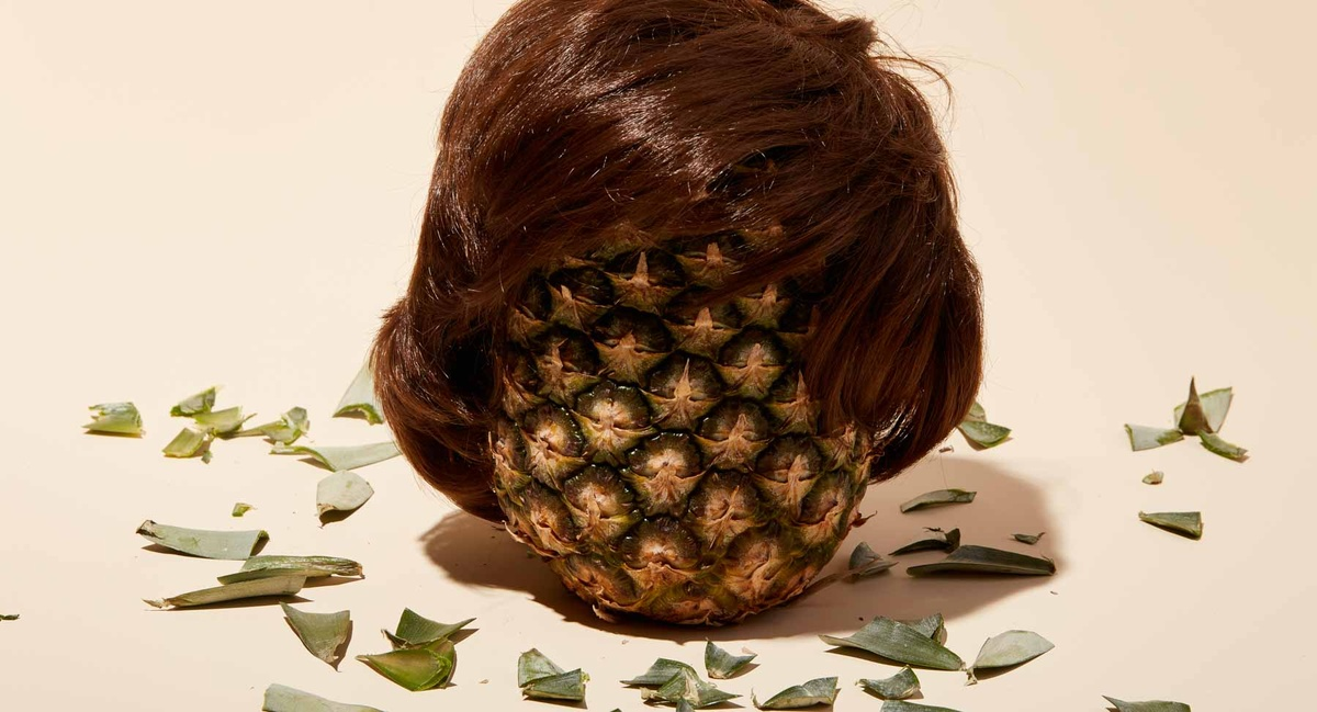 Pinapple with a wig surrounded by leaves