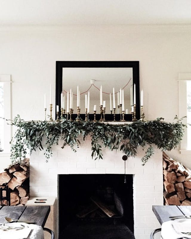 mirror on wall with candles and frames and a holiday garland