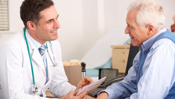 Foto de um senhor de mais idade se consultando com um médico que está sorrindo e segurando laudos nas mãos.