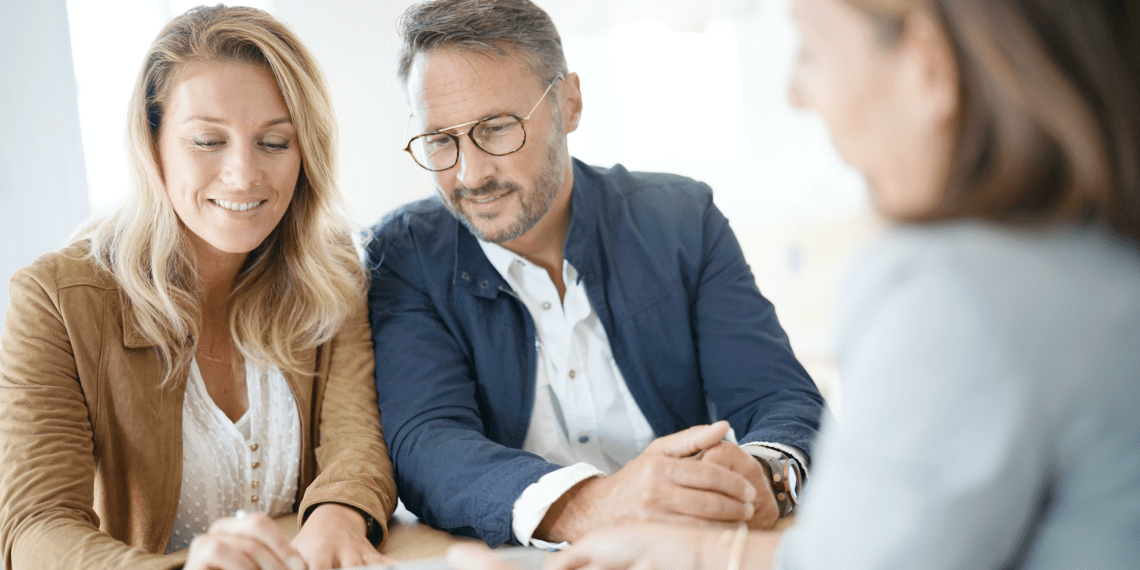 couple looking at document with a broker