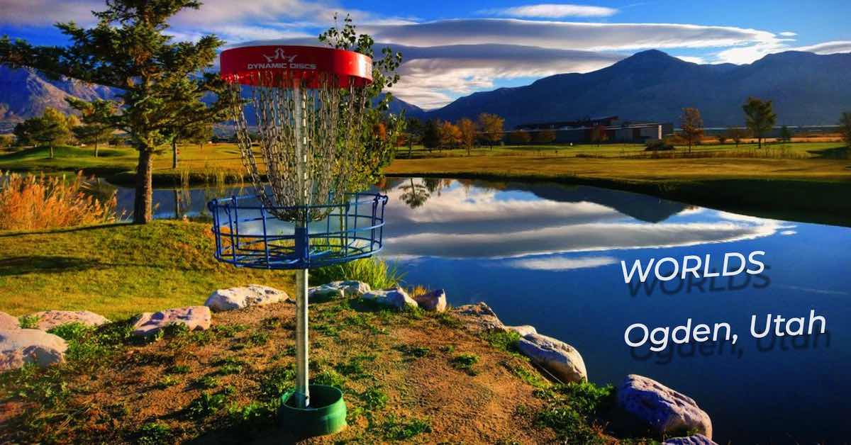 A red and blue disc golf basket near water with a dramatic mountain backdrop near sunset