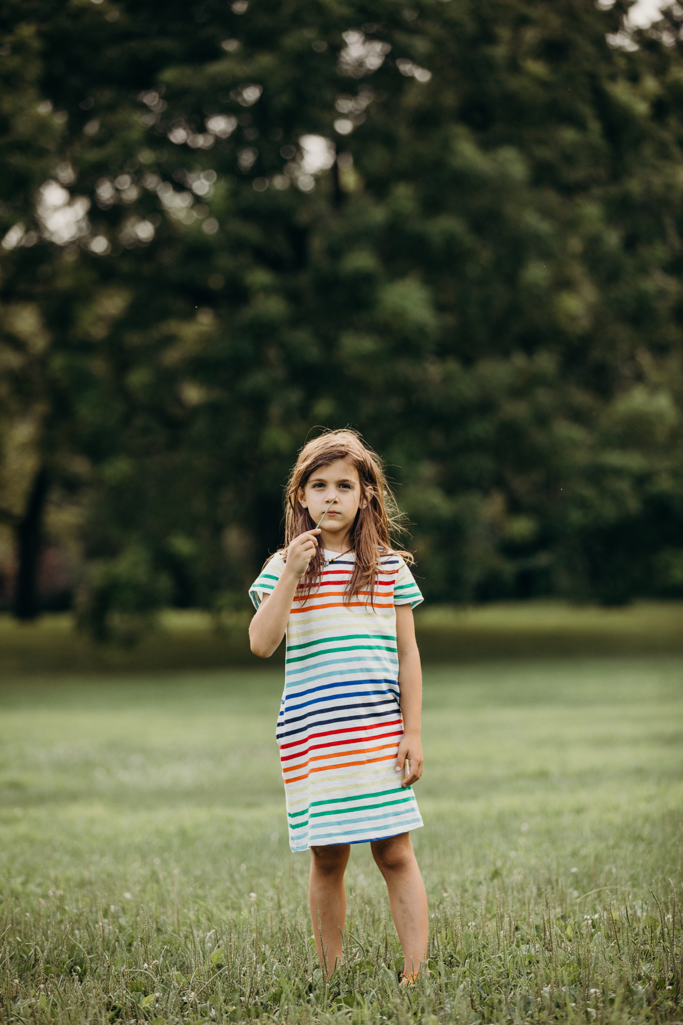 7 year old boy with long hair wearing a rainbow stripe t shirt dress from primary in a park