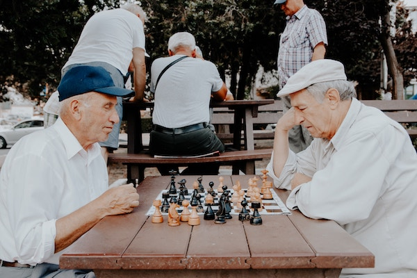 2 elderly men playing chess at an outdoor area for nursing home residents
