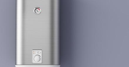 Foto de um aquecedor de inox com termostato no meio e embaixo botões de ajuste. Está pregado em uma parede toda cinza.