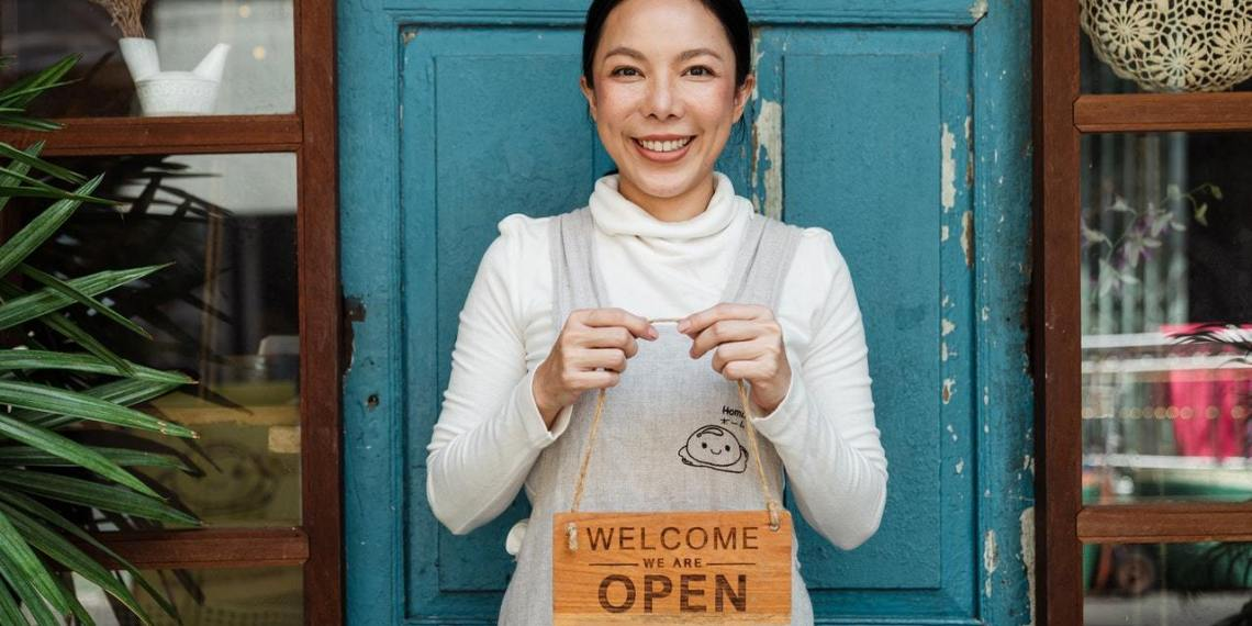 woman holding welcome sign to cafe